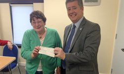 Mr Brown handing over the cheque to Tillicoultry Community Council treasurer, Elma Mitchell, at April's meeting